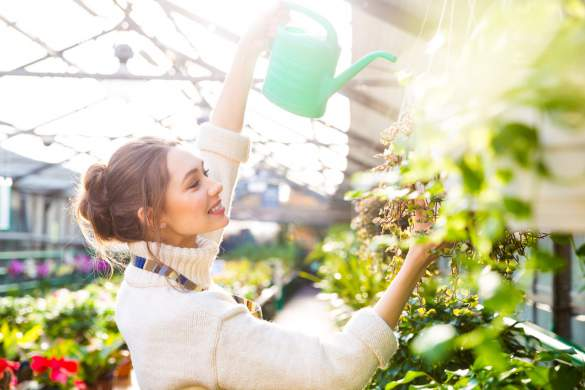 stockfresh_6688772_cheerful-woman-gardener-pouring-flowers-with-watering-can_sizeM